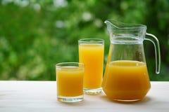 Två exponeringsglas av orange fruktsaft bredvid en karaff Arkivfoton