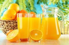 Två exponeringsglas av orange fruktsaft och frukter Arkivfoto