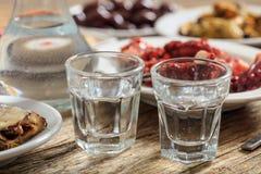 Två exponeringsglas av ouzo och aptitretare arkivfoton