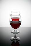 Två exponeringsglas av rött vin med droppar och reflexioner på en glass tabell Arkivbilder