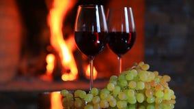 Två exponeringsglas av rött vin med druvor nära spisen stock video