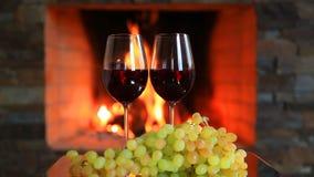 Två exponeringsglas av rött vin med druvor nära spisen arkivfilmer