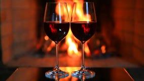 Två exponeringsglas av rött vin nära en spis arkivfilmer