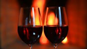 Två exponeringsglas av rött vin nära en spis lager videofilmer