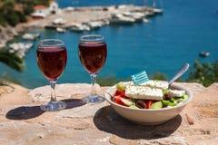Två exponeringsglas av rött vin och bunken av grekisk sallad med den grekiska flaggan på vid havssikten, begrepp för sommargrekfe arkivbild