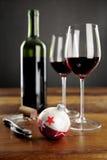 Två exponeringsglas av rött vin och julbaubel Arkivbild