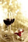 Två exponeringsglas av rött vin och julprydnader royaltyfria bilder