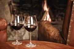 Två exponeringsglas av rött vin på en mysig spis arkivbild