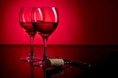 Två exponeringsglas av rött vin på röd och svart bakgrund Arkivbild