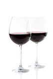 Två exponeringsglas av rött vin på vit Arkivfoton