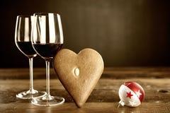Två exponeringsglas av rött vin, pepparkaka och julbaubel Royaltyfri Bild