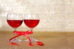 Två exponeringsglas av rött vin som binds samman med pilbåge Royaltyfri Fotografi