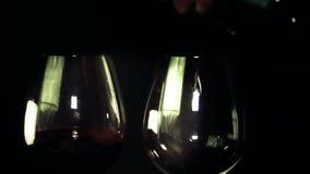 Två exponeringsglas av rött vin som hälls arkivfilmer