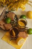 Två exponeringsglas av svart te i glass hållare, några kex, mogna citroner och limefrukter på en linne ytbehandlar mot den ljusa  Royaltyfri Bild