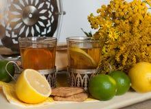 Två exponeringsglas av svart te i glass hållare, några kex, mogna citroner och limefrukter på en linne ytbehandlar mot den ljusa  Arkivbild