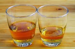 Två exponeringsglas av te eller whisky på en trätabell Arkivfoton