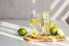 Två exponeringsglas av vatten med citronen och limefrukt på ett träbräde och en blomma av pingstliljan arkivfoto
