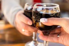 Två exponeringsglas av vin i händerna av mannen och kvinnan med en suddig bakgrund och bokeh Fotografering för Bildbyråer