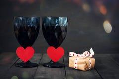 Två exponeringsglas av vin med en pappers- hjärta och en kalender med ett datum på Februari 14 och en gåva På ett trämörker Arkivfoto