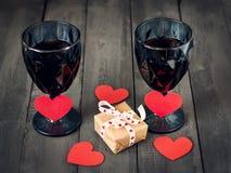 Två exponeringsglas av vin med en pappers- hjärta och en kalender med ett datum på Februari 14 och en gåva På ett trämörker Royaltyfria Foton