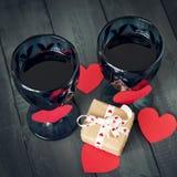 Två exponeringsglas av vin med en pappers- hjärta och en kalender med ett datum på Februari 14 och en gåva På ett trämörker Arkivfoton