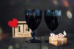 Två exponeringsglas av vin med en pappers- hjärta och en kalender med ett datum på Februari 14 och en gåva På ett trämörker Royaltyfri Bild