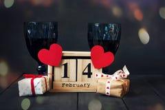 Två exponeringsglas av vin med en pappers- hjärta och en kalender med ett datum på Februari 14 och en gåva På ett trämörker Royaltyfri Fotografi