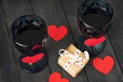Två exponeringsglas av vin med en pappers- hjärta och en kalender med ett datum på Februari 14 och en gåva På ett trämörker Royaltyfria Bilder