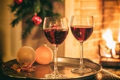 Två exponeringsglas av vin nära en spis royaltyfri foto