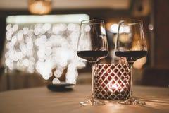 Två exponeringsglas av vin på tabellen nära stearinljuset i aftonen i restaurangen Royaltyfri Fotografi