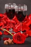 Två exponeringsglas av vin, ros, kronblad och choklader på en svart bakgrund royaltyfria bilder