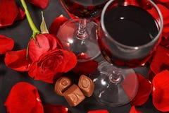 Två exponeringsglas av vin, ros, kronblad och choklader på en svart bakgrund royaltyfri foto