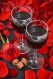 Två exponeringsglas av vin, ros, kronblad och choklader på en svart bakgrund arkivbilder