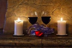 Två exponeringsglas av vin, stearinljus och röd hjärta för nalle på bakgrund för stenvägg red steg livstidsromantiker fortfarande Arkivfoton