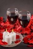 två exponeringsglas av vin, stearinljus och röda rosor på en svart bakgrund royaltyfri foto