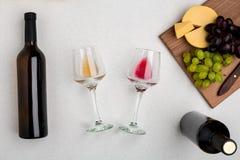 Två exponeringsglas av vit och rött vin, ost och druvor Top beskådar arkivbild