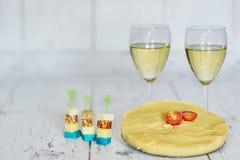 Två exponeringsglas av vitt vin, polenta med den körsbärsröda tomaten och chese canapes på en träbakgrund Fotografering för Bildbyråer