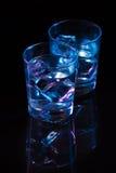 Två exponeringsglas av vodka med iskuber mot bakgrunden av djupblått glöd royaltyfri foto