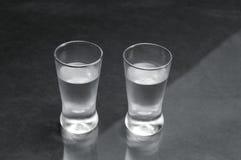 Två exponeringsglas av vodka på den svarta marmortabellen Royaltyfri Bild