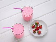 Två exponeringsglas av yoghurt och maträtten med jordgubbar royaltyfri fotografi