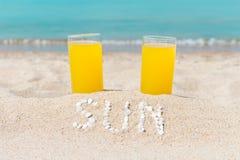 Två exponeringsglas fyllde med fruktsaft på den sandiga stranden, mot bakgrunden av havet Royaltyfri Fotografi