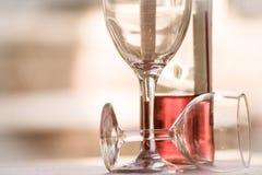 Två exponeringsglas halvfull flaska Rose Wine Daylight Horizontal Fotografering för Bildbyråer