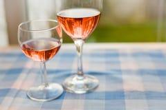 Två exponeringsglas halvfulla röda Rose Wine Blue Checked Table Horizonta Royaltyfri Bild