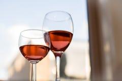 Två exponeringsglas halvfulla röda Rose Wine Brightly Lit Window Horizont Royaltyfri Bild