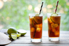 Två exponeringsglas KubaLibre coctail med en cola, en is, en limefrukt och en rom på trätabellen med en sikt till terrassen close royaltyfri bild