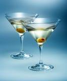Två exponeringsglas martini med oliv. isolerad coctail Arkivbild