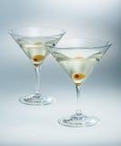 Två exponeringsglas martini med oliv isolerad coctail Arkivfoto