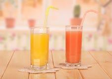 Två exponeringsglas med apelsin- och grapefruktfruktsaft arkivbild
