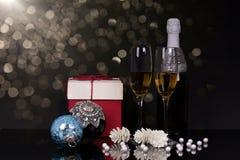 Två exponeringsglas med champagne, gåvan och julprydnader royaltyfri fotografi