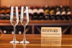 Två exponeringsglas med champagne i bakgrund med flaskor av vin Royaltyfri Bild
